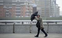 A commuter loses control of his umbrella as he braves the wind and rain while crossing London Bridge in London